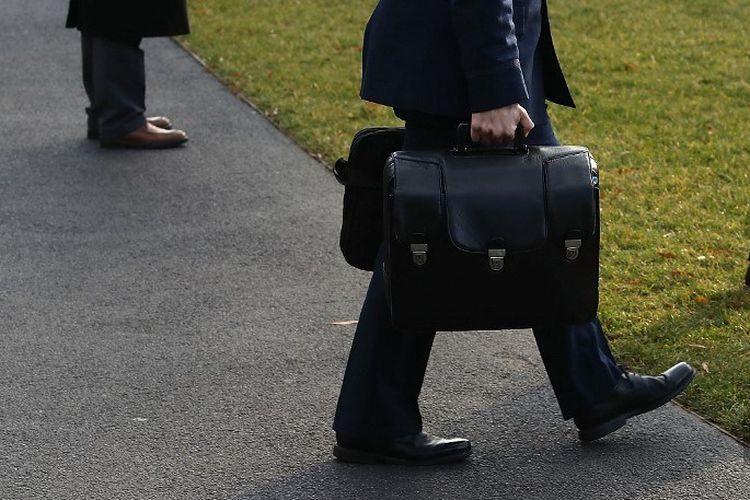Seorang ajudan militer membawa koper nuclear football saat berjalan menuju helikopter Marine One, untuk berangkat bersama Presiden Amerika Serikat Donald Trump pada 2 Desember 2017 di Washington DC.