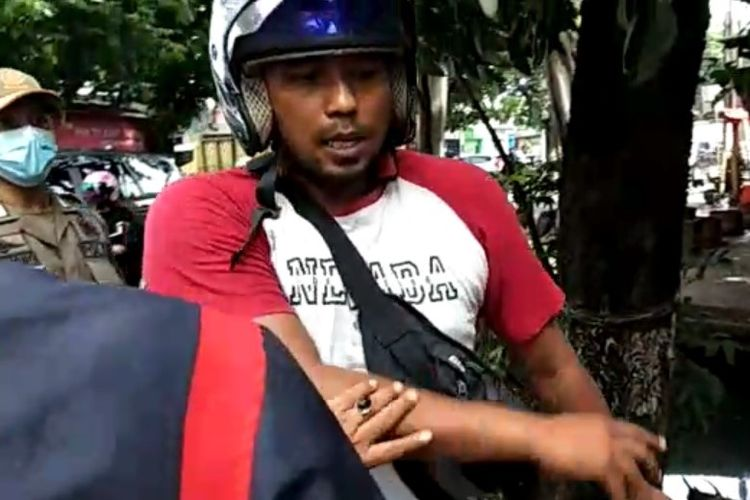 Salah satu pemotor di daerah Cibubur, Jakarta Timur, dirazia petugas Satpol PP karena tidak memakai masker.