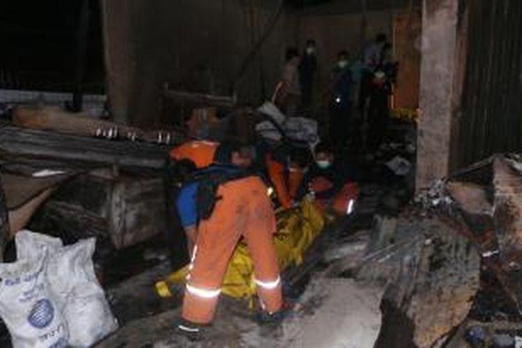Petugas mengevakuasi satu jenazah korban tewas dalam kebakaran di toko material Jalan Kemang Utara 9, Duren Tiga, Jakarta Selatan, Senin (23/9/2013).