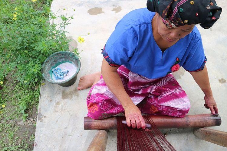 langkah pertama dalam membuat kain ulos secara tradisional. Yaitu melumuri benang supaya benangnya kuat