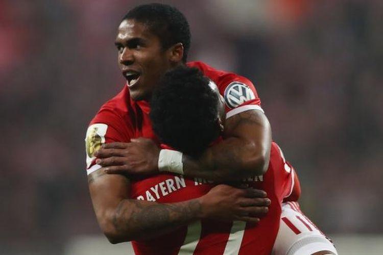 Douglas Costa dan David Alaba merayakan mencetak gol penentu kemenangan Bayern Muenchen atas Wolfsburg pada partai babak 16 besar DFB Pokal di Allianz Arena, Selasa (7/2/2017).