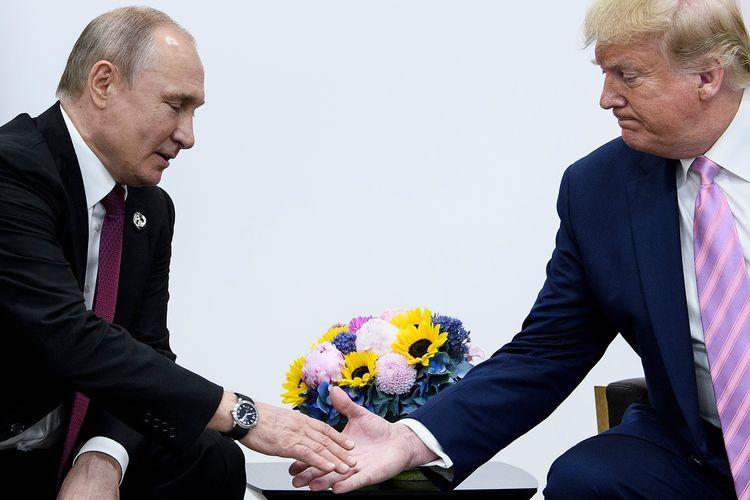 Presiden Rusia Vladimir Putin ketika berjabat tangan dengan Presiden Amerika Serikat Donald Trump di selam KTT G20 di Osaka, Jepang, pada Jumat (28/6/2019).