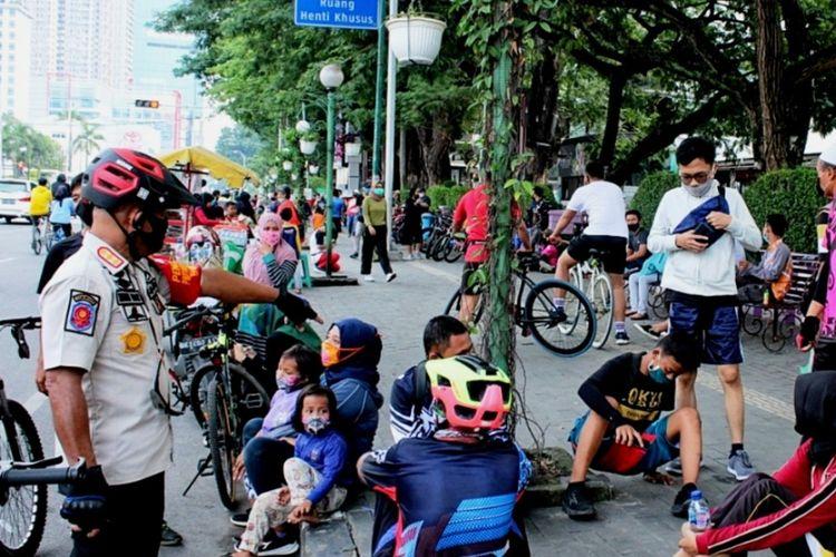 Kepala Satpol PP Pemprov Sumut Suriadi Bahar menertibkan para pesepeda dan warga yang membawa balita di seputaran Lapangan Merdeka Medan, Senin (27/7/2020)