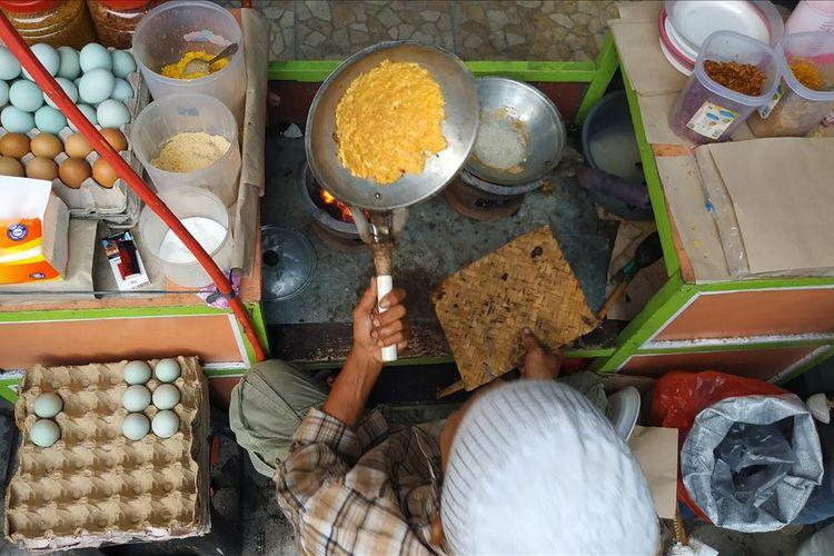 Pedagang kerak telor di Pekan Raya Jakarta tampak sibuk menyelesaikan pesanan pembeli.