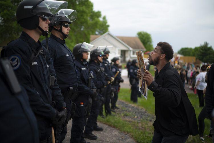 Seorang demonstran membawa papan bertuliskan kalimat protes, berhadapan dengan jajaran polisi yang mengamankan rumah Derek Chauvin, polisi Minneapolis yang dipecat setelah membunuh pria kulit hitam George Floyd. Foto diambil pada Rabu (27/5/2020).