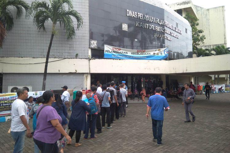 Masyarakat mengantre untuk membauar pajak kendaraan di Samsat Kebon Nanas, Jakarta Timur, Selasa (12/11/2017)