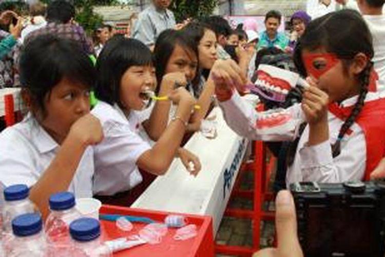 Anak-anak SD Babakan Madang 1, Sentul, Bogor, menyikat gigi bersama pada perayaan Hari Kesehatan Gigi Sedunia pada 20 Maret 2015.