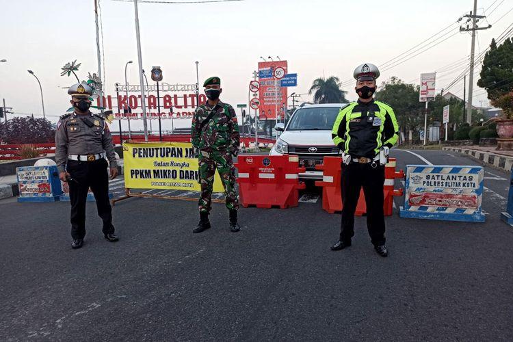 Petugas berjaga di titik penyekatan yang merupakan salah satu pintu masuk ke wilayah Kota Blitar, Sabtu (24/7/2021)