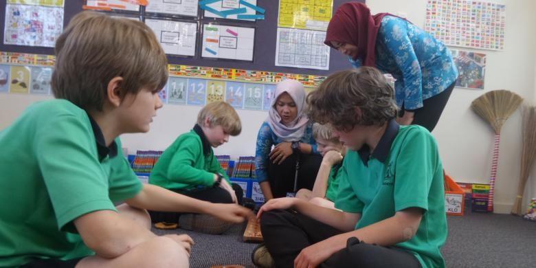 Anak-anak usia sekolah dasar di Turner School mengikuti pelajaran Bahasa Indonesia melalui permainan tradisional congklak. Dyah Candra Arbiningrum dan rekannya, guru dari Pangkalan Bun, Kalimantan Tengah, ikut mengajar sebagai guru pendamping saat mengikuti program Bridge.