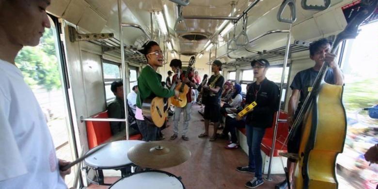 Satu grup pengamen dengan beragam alat musik beraksi di dalam kereta api Commuter Line KRL Ekonomi dari arah Bekasi ke Manggarai, Rabu (21/3/2012).