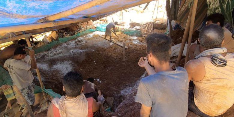 Penambang rakyat menabur kapur di atas kolam berlapis terpal yang berisi tanah untuk proses penjernihan tanah yang akan diberi air.