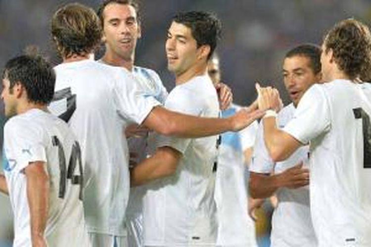 Striker Uruguay, Luis Suarez (tengah) merayakan gol yang dicetaknya ke gawang Jepang pada laga persahabatan di Miyagi Stadium di Rifu, Rabu (14/8/2013). Uruguay menang 4-2.