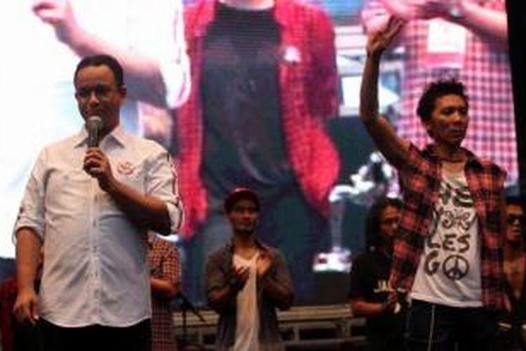 Akademisi Anies Baswedan (kiri) bersama personil Slank Bimbim menghadiri konser 'Revolusi Harmoni, Revolusi Mental' bersama musisi Indonesia lainnya di Senayan, Jakarta, Rabu (11/6/2014). Konser tersebut digelar untuk mendukung pasangan Joko Widodo dan Jusuf Kalla dalam Pilpres 9 Juli mendatang.