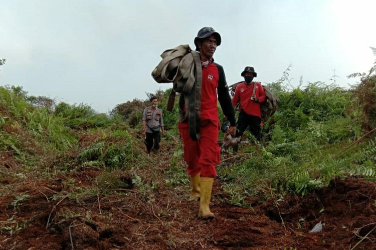 Tim Manggala Agni Sumatera V Daops Dumai memikul peralatan pemadaman untuk memadamkan titik api karhutla di Desa Sukarjo Mesim, Kecamatan Rupat, Kabupaten Bengkalis, Riau, Selasa (23/2/2021).