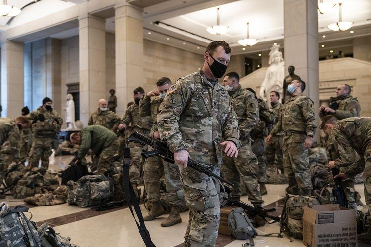 Ratusan pasukan Garda Nasional berada di dalam Pusat Pengunjung Capitol untuk memperkuat keamanan Gedung Capitol di Washington DC, Rabu (13/1/2021). DPR AS sedang mengejar artikel pemakzulan terhadap Presiden AS Donald Trump atas perannya dalam menghasut massa untuk menyerbu Gedung Capitol pekan lalu.