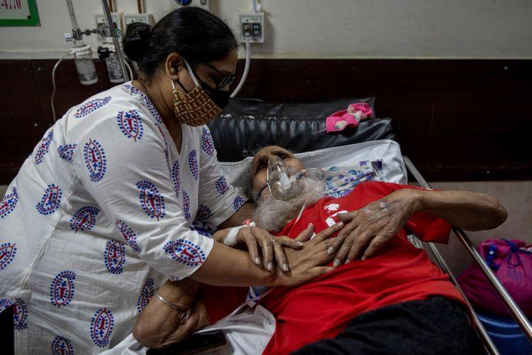 Seorang pria yang menderita penyakit virus corona (Covid-19) dihibur oleh putrinya saat ia menerima perawatan di dalam bangsal korban di sebuah rumah sakit di New Delhi, India, Sabtu (1/5/2021).