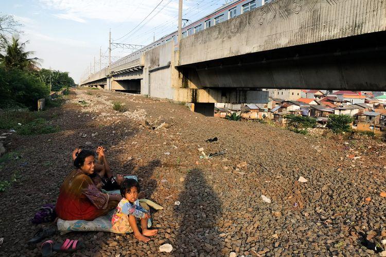Keluarga Waluyo bercengkerama sambil menghabiskan sore hari di pinggir rel kereta Manggarai-Cikarang tepatnya di kawasan Manggarai, Tebet, Jakarta Selatan pada Jumat (13/3/2021) sore. Keluarga Waluyo merupakan potret keluarga yang termarjinalkan di ibu kota.