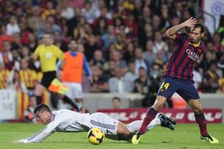 Penyerang Real Madrid, Cristiano Ronaldo, terjatuh saat dilanggar gelandang Barcelona, Javier Mascherano, saat kedua tim bertemu dalam lanjutan Liga BBVA di Camp Nou, Sabtu (26/10/2013). Wasit Alberto Undiano tak menilai kejadian tersebut sebagai sebuah pelanggaran sehingga Madrid tak mendapatkan hadiah penalti.