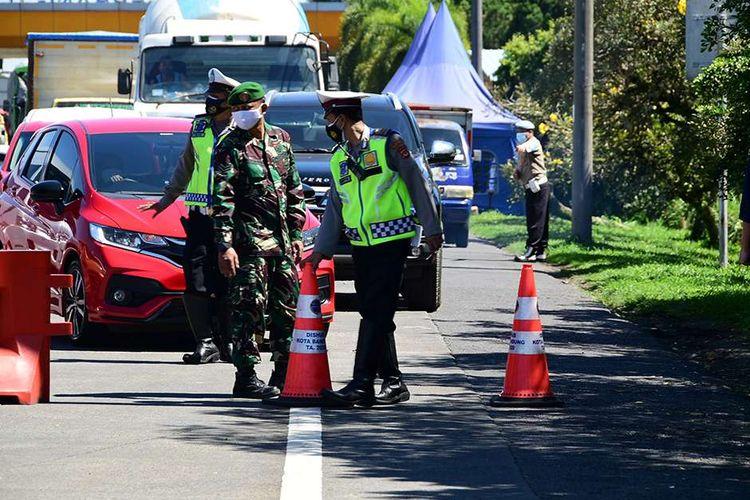 Petugas melakukan penyekatan kendaraan di depan Gerbang Tol Pasteur, Kota Bandung, Jawa Barat, Selasa (6/7/2021). Selama PPKM Darurat, Kota Bandung tertutup bagi warga dari luar wilayahnya, hal tersebut dilakukan untuk menekan mobilitas masyarakat dan mengurangi penyebaran Covid-19.