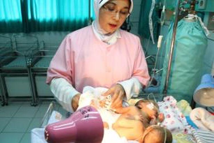 Seorang perawat RSUD Gambiran Kota Kediri, Jawa Timur tengah menangani bayi perempuan kembar siam yang lahir di rumah sakit itu, Senin (15/7/2013).