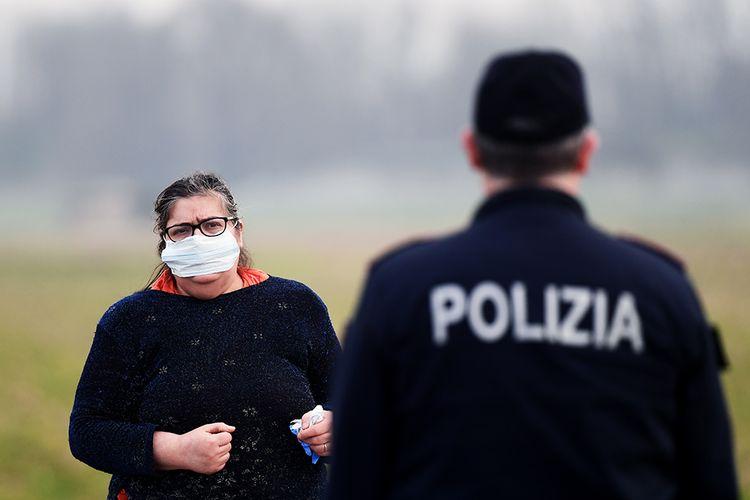 Warga mengenakan masker guna mengantisipasi penyebaran virus corona saat berbicara dengan petugas polisi di kota kecil Italia, Casalpusterlengo, Minggu (23/2/2020). Penyebaran virus corona hingga hari ini, Senin (24/2/2020), semakin menunjukkan peningkatan di sejumlah negara, seperti Italia, Iran, dan Korea Selatan.