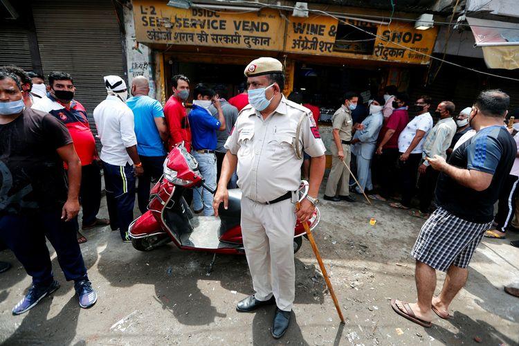 Seorang polisi, mengenakan maker dan membawa tongkat pemukul, berdiri di depan toko minuman keras di New Delhi, pada 4 Mei 2020. Warga mengantre membeli alkohol setelah India melonggarkan aturan lockdown guna memerangi Covid-19.