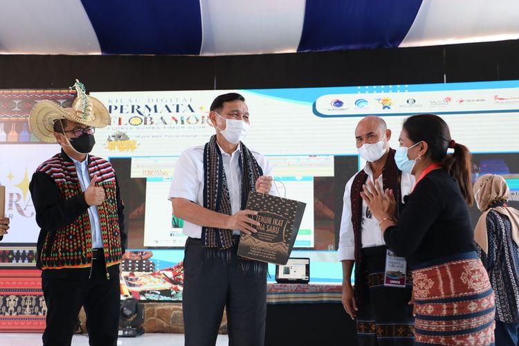 Menteri Koordinator Bidang Kemaritiman dan Investasi Luhut Binsar Pandjaitan (tengah) didampingi Direktur Strategic Portfolio Telkom Budi Setyawan Wijaya (paling kiri) melakukan pembelian produk UMKM Tenun Ikat Ina Sabu melalui pameran virtual pada acara puncak Gerakan Nasional Bangga Buatan Indonesia (Gernas BBI) yang mengusung tema Kilau Digital Permata Flobamora di Manggarai Barat, Jumat (18/6/2021).