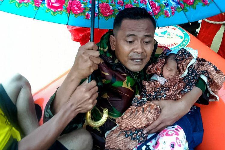 Prajurit TNI dari Koramil 14 Rantau Peureulak, Aceh T imur, menyelamatkan bayi yang baru lahir empat hari di lokasi banjir Desa Alue Bate, Kecamatan Rantau Peureulak, Aceh Timur