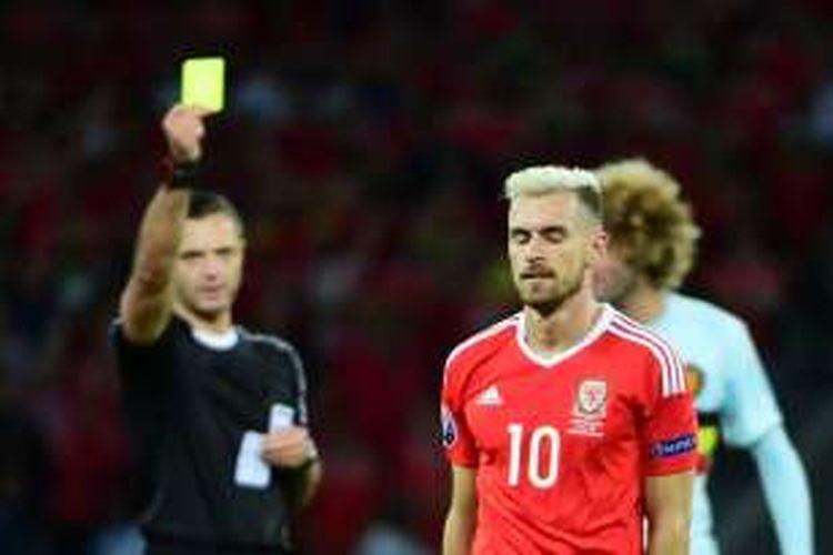 Gelandang Wales, Aaron Ramsey, menerima kartu kuning saat timnya melawan Belgia pada perempat final Piala Eropa di Stade Pierre-Mauroy, Jumat (1/7/2016).