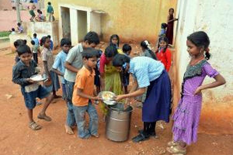 Anak-anak sekolah dasar di Bangalore, India sedang mengantre makan siang gratis dari sekolah, Jumat (19/7/2013). Program makan siang gratis ini marak digelar sekolah-sekolah di India, karena separuh anak-anak di sana terindikasi kurang gizi. Sayangnya, anak-anak ini pun terancam makanan yang dimasak tak higienis.