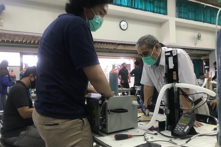 Pencipta Vent-I, Syarif Hidayat (kemeja putih)  tengah melihat proses pengerjaan ventilator portable.