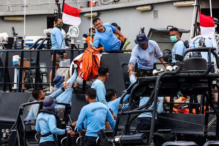 Prajurit TNI AL memindahkan kantong berisi temuan puing ke KRI Rigel-933 saat pencarian korban dan puing pesawat Sriwijaya Air nomor penerbangan SJ 182 di perairan Kepulauan Seribu, Jakarta, Selasa (12/1/2021). Pada hari keempat pencarian tim SAR menambah satu kapal untuk memperkuat operasi pencarian korban, puing, dan kotak hitam pesawat Sriwijaya Air SJ182 menjadi 54 kapal.