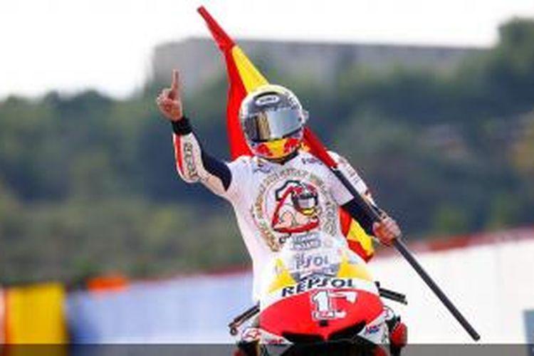 Pebalap Repsol Honda asal Spanyol, Marc Marquez mengangkat bendera setelah memastikan gelar Juara Dunia MotoGP 2013 dengan finis ketiga pada GP Valencia, Minggu (10/11/2013).