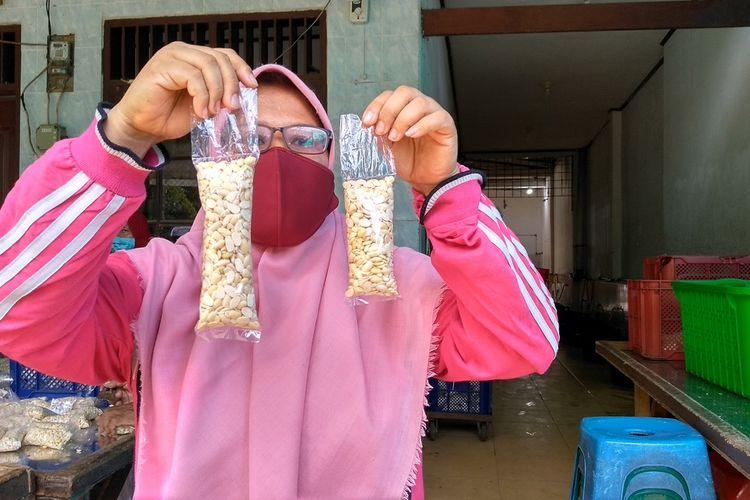 Adhe Putri menunjukkan produksi tempe ukuran 0,7 ons dan 0,9 ons. Melonjaknya harga kedelai membuatnya terpaksa mengecilkan ukuran tempe.