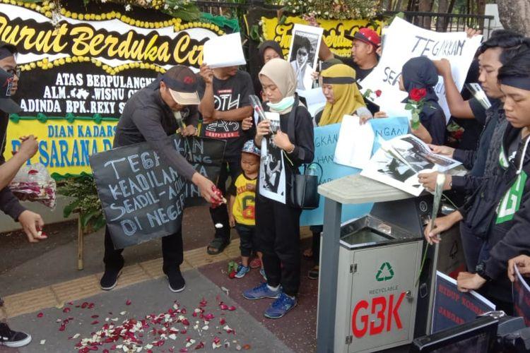 Keluarga dan kerabat pengguna skuter listrik GrabWheels yang tewas ditabrak, Wisnu (18) dan Ammar (18), menggelar aksi tabur bunga di Pintu 3 Gelora Bung Karno, Senayan, Jakarta, Minggu (17/11/2019).