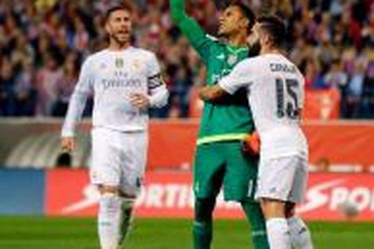 Sergio Ramos dan Daniel Carvajal menyelamati Keylor Navas yang menahan tendangan penalti Antoine Griezmann, Minggu (4/10/2015).