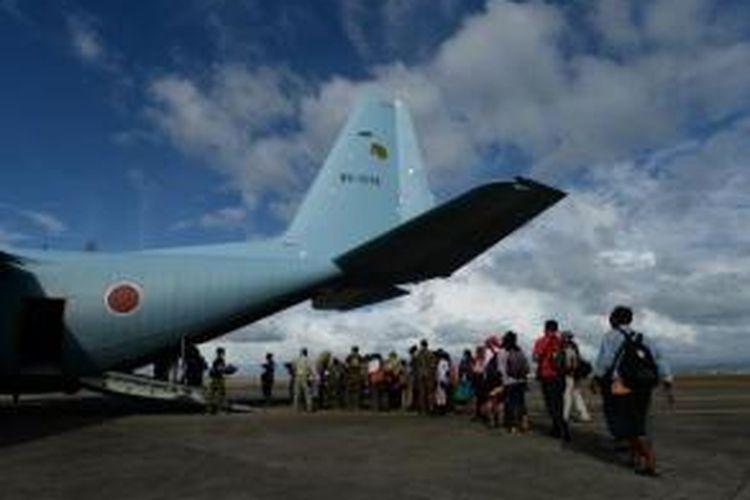Sejumlah pengungsi korban bencana topan Haiyan, memasuki pesawat angkut militer Hercules C-130 milik Jepang di Bandara Tacloban, Leyte, Filipina. Pesawat ini akan membawa para pengungsi menuju kota Cebu.