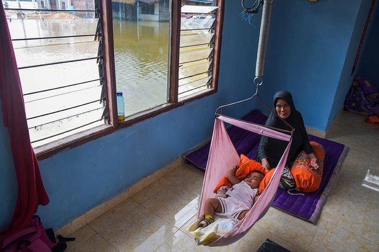 Seorang nenek menidurkan cucunya saat mengungsi di mushala di Desa Sahilan Darussalam akibat rumahnya banjir luapan Sungai Subayang di Kecamatan Gunung Sahilan Kabupaten Kampar, Riau, Rabu (11/12/2019). Berdasarkan data Badan Penanggulangan Bencana Daerah (BPBD) Kampar, tingginya intensitas hujan mengakibatkan air sungai meluap sehingga membanjiri dua desa di Kecamatan Gunung Sahilan, akses jalan desa terputus dan sekitar 276 kepala keluarga terdampak banjir.