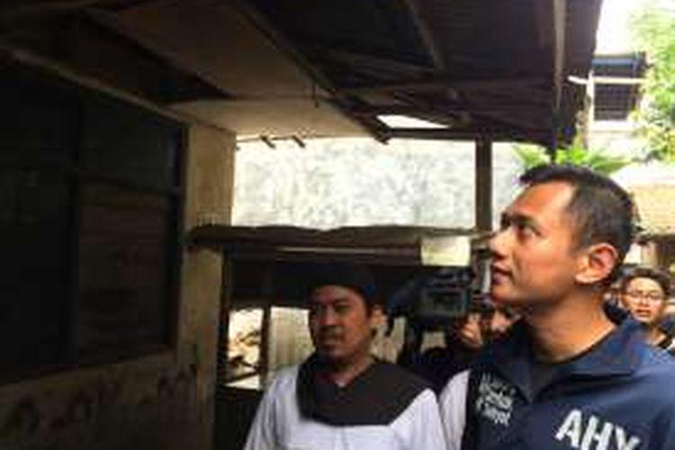 Cagub DKI Jakarta, Agus Harimurti Yudhoyono saat melihat rumah kosong yang ditinggal penghuninya karena banjir di RT 05/07, Tegal Parang Selatan, Jakarta Selatan, Rabu (7/12/2016).