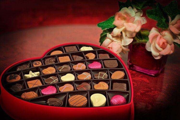 Ilustrasi cokelat dalam boks berbentuk hati.