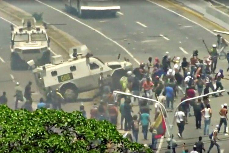 Kendaraan dari Garda Nasional Venezuela (GNB) menghantam kerumunan pendemo yang menggelar aksi protes di Caracas pada 30 April.