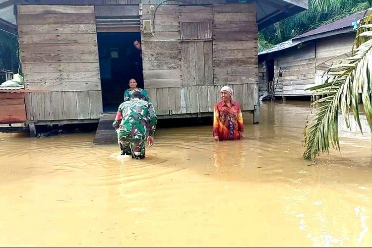 Babinsa Koramil 10/Kunto Darussalam Kopda Jantri Istani memantau dan mendata warga yang dilanda banjir di Desa Kasang Mungkal, Kecamatan Bonai Darussalam, Kabupaten Rohul, Riau, Senin (29/3/2021).