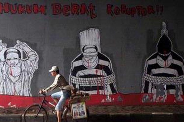 Warga melintas di depan poster berisi kritikan hukuman yang berar terhadap koruptor di Bekasi, Jawa Barat, Sabtu (19/1/2013). Kritikan terhadap pelaku koruptor terus disuarakan oleh aktivis untuk mendorong tindakan lebih tegas dalam pemberantasan korupsi tanpa pandang bulu. KOMPAS/AGUS SUSANTO
