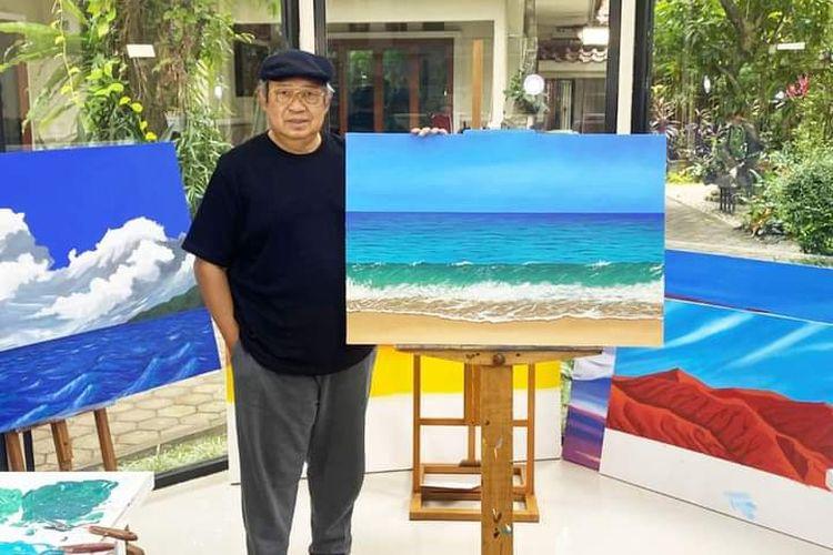 Presiden keenam RI Suilo Bambang Yudhoyono (SBY) berpose di antara sejumlah karya lukisannya di Cikeas, Bogor, Sabtu (7/8/2021).