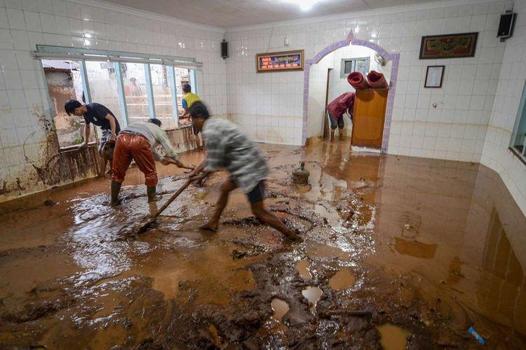 Warga membersihkan lumpur di dalam musala akibat banjir bandang di Kecamatan Jatihandap, Bandung, Jawa Barat, (20/3/2018). Banjir bandang yang disertai lumpur tersebut disebabkan oleh luapan Sungai Cipamokolan akibat intensitas hujan yang tinggi di beberapa wilayah Kota Bandung.
