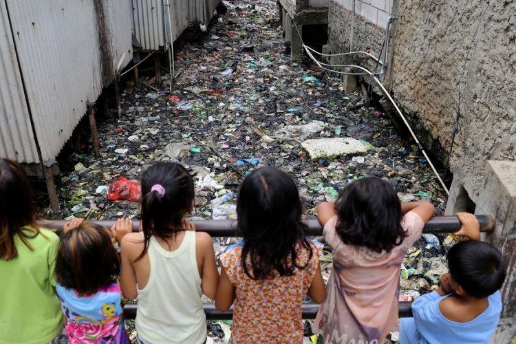 Sejumlah anak bermain di Kali Gendong, Waduk Pluit, Penjaringan, Jakarta Utara, Selasa (14/3/2017). Kurangnya kesadaran masyarakat membuang sampah sembarangan mengakibatkan sampah plastik dari rumah tangga nyaris menyerupai daratan tersebut menumpuk di sepanjang Kali Gendong.