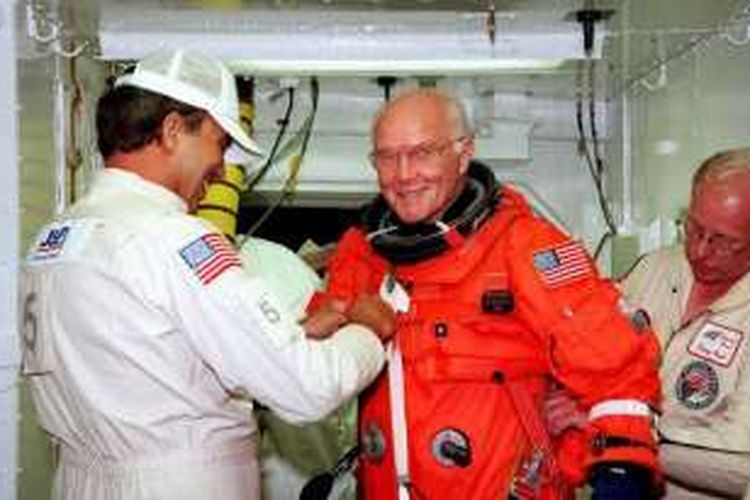 Dalam foto yang diambil pada 9 Oktober 1998 ini terlihat John Glenn mendapatkan bantuan dari para teknisi sebelum naik ke pesawat ulang alik Discovery.