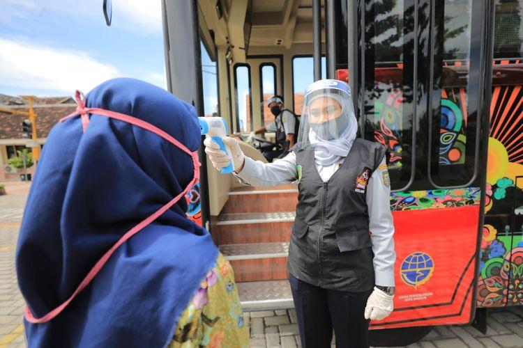 Pendekar Waras memeriksa suhu tubuh warga sebelum menumpang bus wisata gratis Mabour di Kota Madiun.