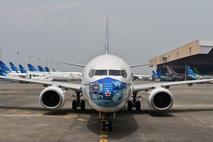 Pesawat Garuda Indonesia Boeing 373-800 NG dengan desain masker di bagian depan pesawat, saat diparkir di lapangan udara di Tangerang, Banten, Senin (12/10/2020). Pemasangan masker di pesawat tersebut digelar untuk mendukung kampanye Gerakan Ayo Pakai Masker dalam rangka penanggulangan pandemi Covid-19.