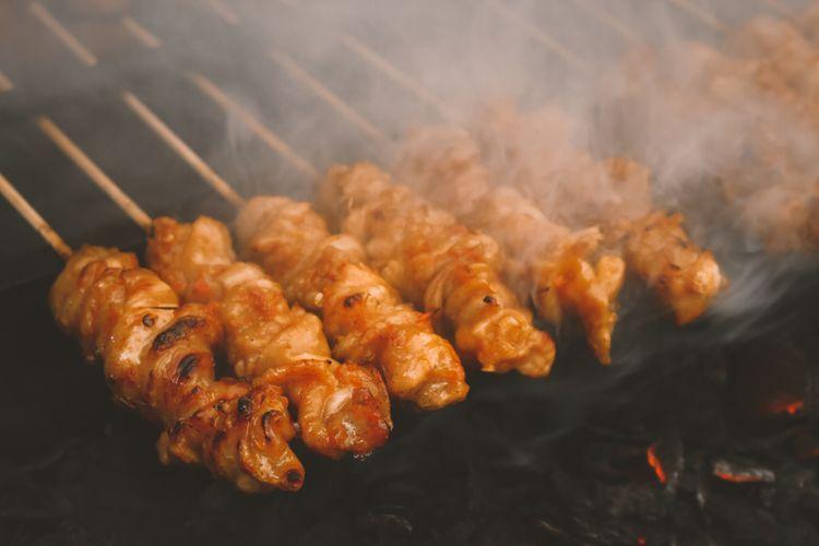 Ilustrasi sate kulit ayam sedang dibakar.